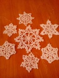 Для создания неповторимой праздничной новогодней атмосферы украсьте дом или елку ажурными снежинками ручной работы. Предлагается набор из 7 снежинок: одна большая (10-12 см) и шесть меньше размером (5-7 см). Снежинки связаны из хлопка и жестко накрахмалены. Замечательно держат форму. Крепятся на тонкие золотые нити.