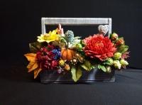 Великолепный яркий, красочный букет из осенних цветов и тыквы. В составе: ягоды голубики, ежевики, лесной орех, хмель, георгин, розы, антуриумы и чернобривцы. Такая яркая композиция придаст вашему интерьеру особый, незабываемый шарм, улучшит настроение, снимет депрессию, а также послужит символом благополучия, плодородия, изобилия.