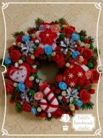 В работе использованы: венок из ели 32 см, игрушки из фетра 7 см (4 шт.) в красно-белой гамме, розы красные из фоамирана 4 см, помпоны зеленые и красные 1 см, шишки натуральные сосновые, белая акриловая краска, розы красные, голубые и персиковые с фатином,  анис натуральный, палочки корицы 5 см, подснежники красные и белые с чашелистиками, деревянные снежинки, шишки казуарина натуральные отбеленные 1-3 см.